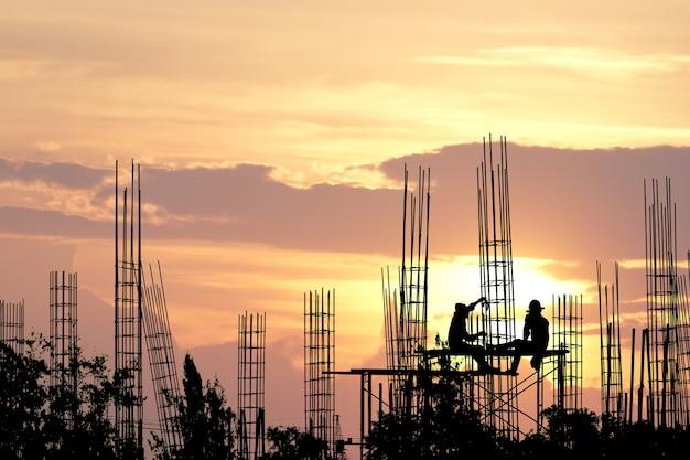 安全上の労働者のシルエットは工事現場で高い地面と鋼鉄棒から立ちます。 Premium写真