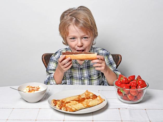 チョコレートとフランスパンを食べる少年 Premium写真