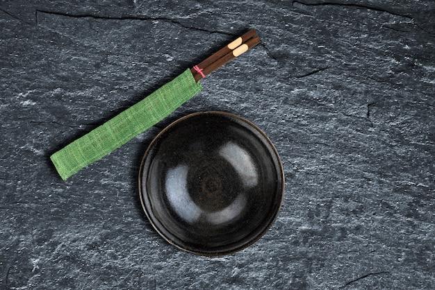空のボウルと背景テクスチャ上の箸 Premium写真