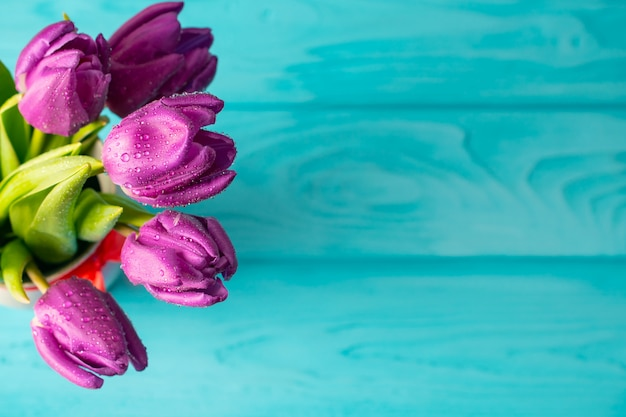 青い木製の背景、ホリデーカードに美しい新鮮な紫チューリップの旅 Premium写真