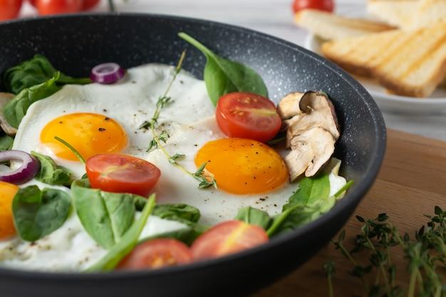 目玉焼き、トマト、マッシュルーム、ほうれん草の葉のヘルシーな朝食 Premium写真