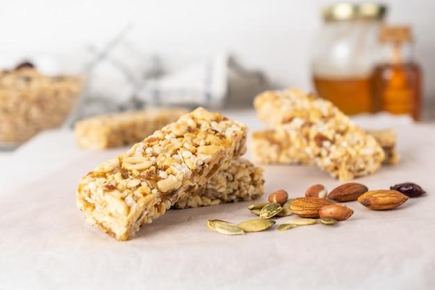 ナッツ、蜂蜜、木製のテーブルの乾燥果実と健康的な自家製グラノーラバー Premium写真