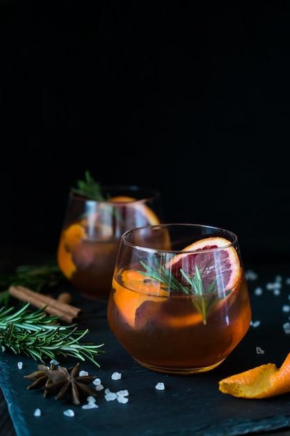 黒のネグローニカクテルにオレンジとローズマリーのスライスを添えて。 Premium写真
