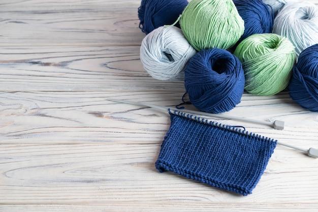 青と緑の糸と白い木製の針で趣味の組成を編む Premium写真
