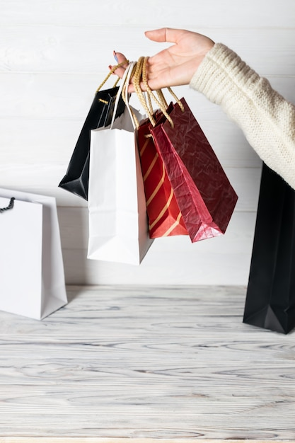 手にショッピングパッケージを保持している幸せな女。紙袋。店頭での販売。顧客がプレゼントを購入します。ブラックフライデーのセール。休日の特別オファー、割引。市場の女性 Premium写真