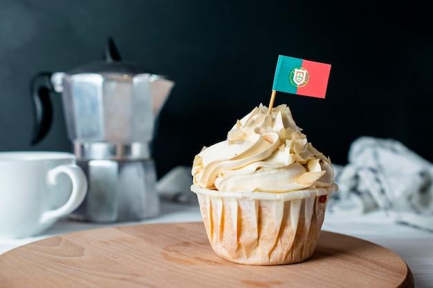 焼きたてのアーモンドクリームカップケーキとアーモンドクラム、モーニングティーパーティーのポルトガル国旗 Premium写真