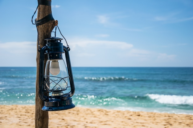 晴れた日の背景に海とビーチの列に青いランタン Premium写真