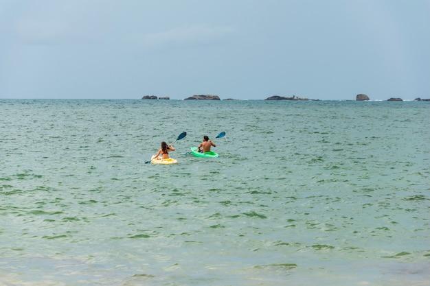 カップルは、海や海でカヤックやカヌーで泳ぎます。人々とカヤックやカヌーのコンセプト。テキスト用のスペース Premium写真