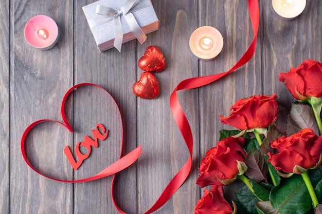 美しい赤いバラと愛のレタリングの花束とロマンチックな聖バレンタイン木製の背景カード Premium写真