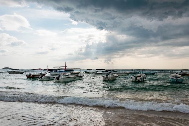 海または海沿いの多くの伝統的なボートやヨット。差し迫った熱帯性暴風雨と空の空と暗い雨雲とそれらを突破する太陽 Premium写真