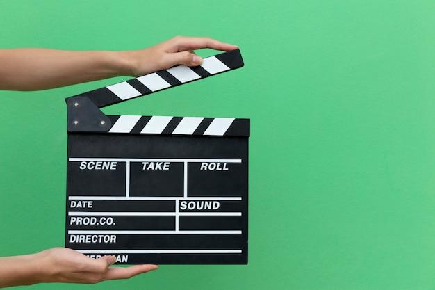 手は映画を叫ぶための映画クラッパーボードスレート機器フィルムアクションを取ります。 Premium写真