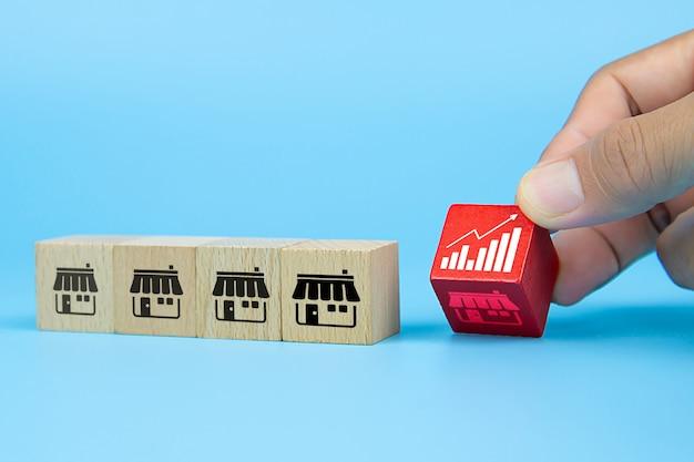 Рука бизнесмена выбирая блог игрушки куба деревянный с значком диаграммы от магазина значков франшизы маркетинга Premium Фотографии