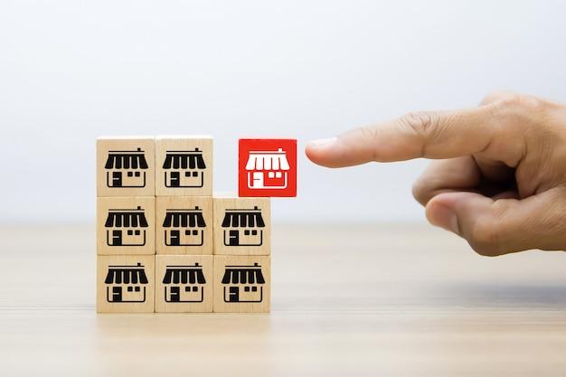 Рука бизнесмена выбирает деревянный блог с магазином значков маркетинга франшизы. Premium Фотографии