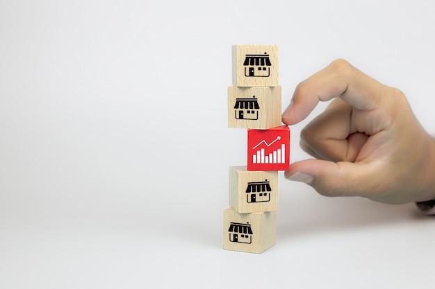 Рука выбирает значок диаграммы с магазином значков маркетинга франшизы на блоге игрушки куба деревянном штабелирована для роста бизнеса и стратегии расширения ветви финансовой. Premium Фотографии