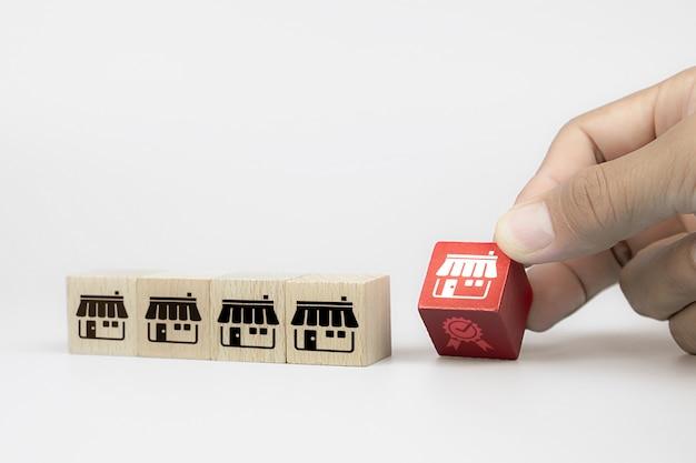Рука выбирает куб деревянные игрушки блоги с франшизой маркетинговой магазин значок и значок диаграммы. Premium Фотографии