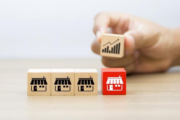 Блог игрушки куба деревянный с значком магазина маркетинга франшизы и рука выбирая значок диаграммы позади. Premium Фотографии