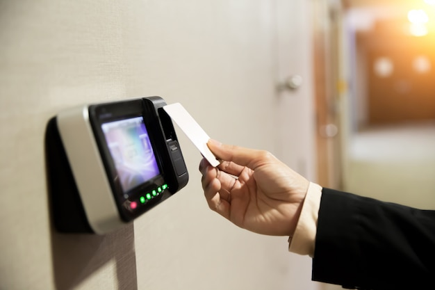 キーカードを使用してドアを開く手実業家のクローズアップ。 Premium写真