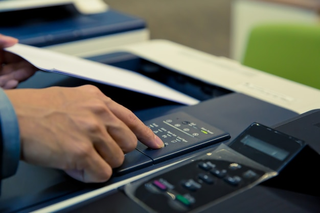 クローズアップショットビジネスマンはコピー機を使用しています。 Premium写真
