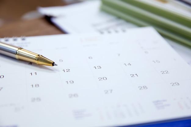 机の上のペンとカレンダーを閉じます。 Premium写真