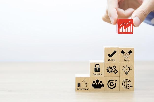 Рука выбирает значок графика графический на деревянном блоке. Premium Фотографии