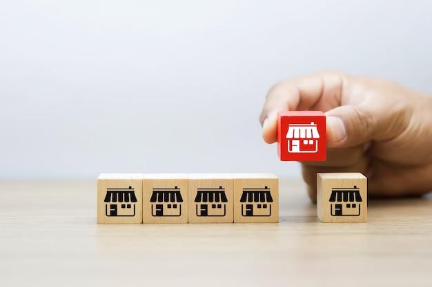 Рука выбирает магазин икон франшизы на деревянном блоге. Premium Фотографии