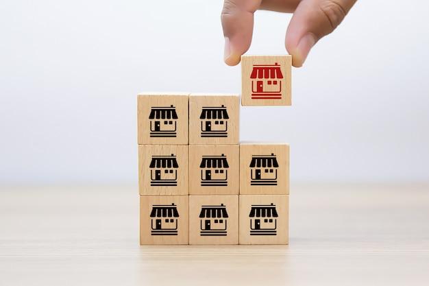Рука выбрать деревянный блог с магазином икон франшизы Premium Фотографии