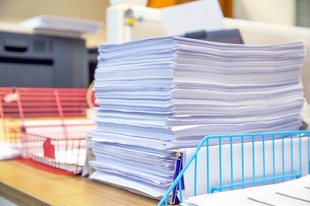 デスクオフィスにたくさんの書類が山積みになっています。 Premium写真