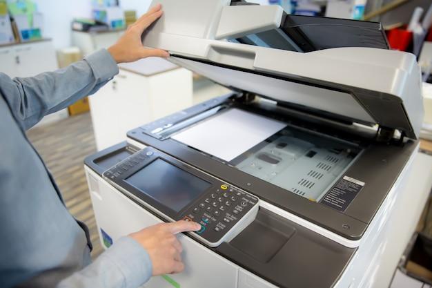 ビジネスマンはコピー機を使用しています。 Premium写真