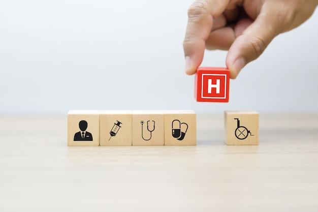 手は、木製ブロックの医療と健康のアイコンを選択します。 Premium写真