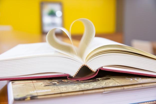 図書室のテーブルにハート形の本の画像を閉じます。 Premium写真