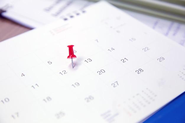 Красный штифт на календарь для бизнеса и встречи планировщик. Premium Фотографии