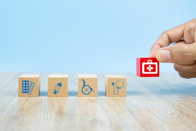 クローズアップ手は木のおもちゃのブロックにヘルスケアと医療のシンボルアイコンを選択します。 Premium写真