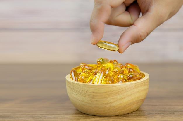 Ручной выбор капсулы масла печени трески из кучи жира пищевой добавки рыбьего жира или рыбьего жира для концепции здравоохранения. Premium Фотографии