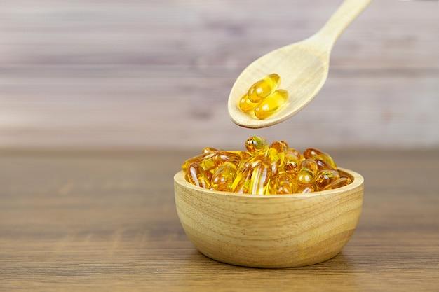 Куча капсулы масла печени трески в чашке и деревянной ложке. пищевая добавка для концепций здравоохранения. Premium Фотографии