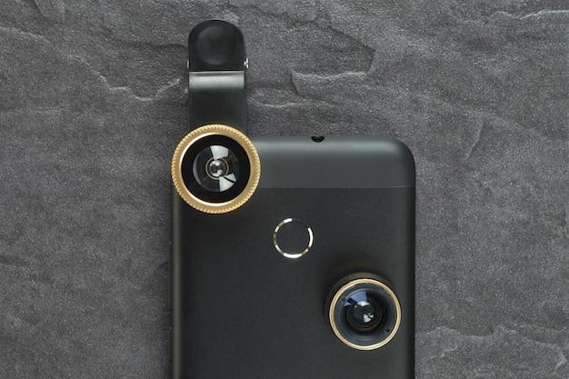 余分なレンズを備えたモダンなスマートフォン。上からの眺め。 Premium写真