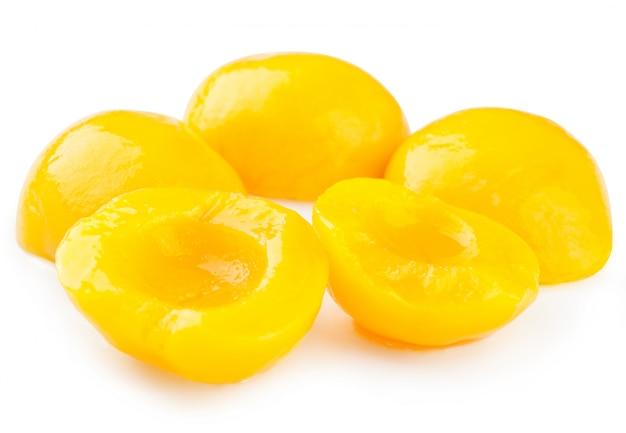 Консервированные персики на белом фоне. Premium Фотографии