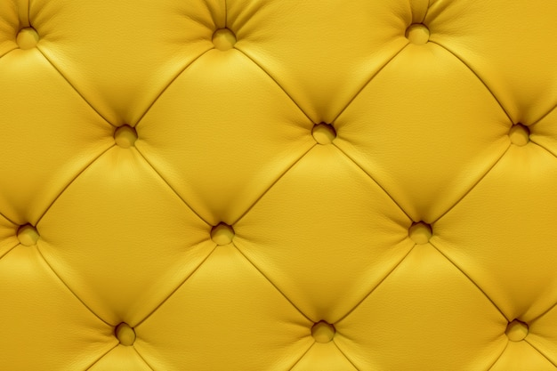 黄色の革のソファ、ステッチボタンの背景。 Premium写真