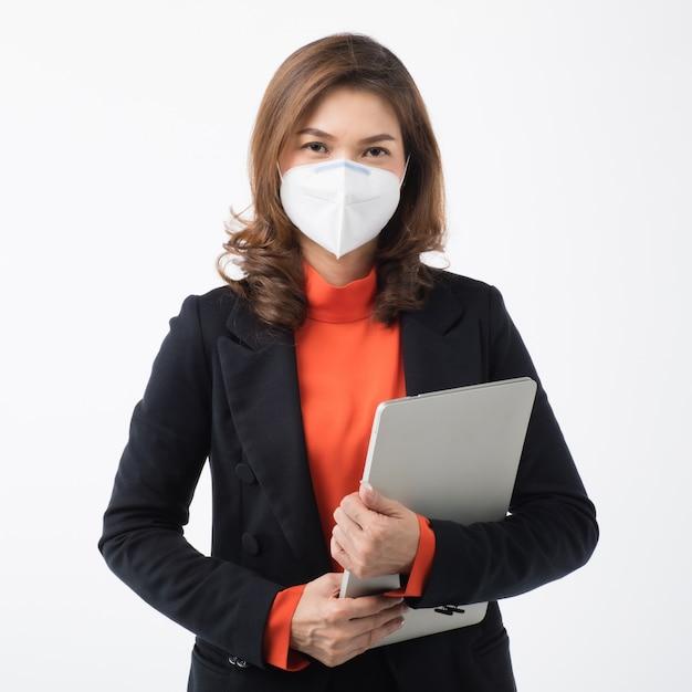スーツのビジネスウーマンはコンピューターを保持し、マスクを使用してコロナウイルスから保護します Premium写真