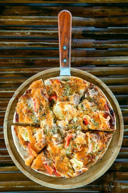 竹のテーブルの木製プレートのピザ。 Premium写真