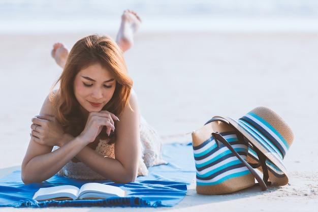 アジアの女性はビーチに敷設と読書 Premium写真