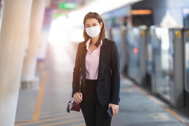 電車を待っているマスクを身に着けている女性実業家。 Premium写真