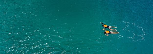カップルは海で泳ぐ Premium写真