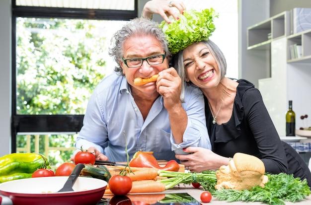 Пожилая пара весело на кухне со здоровой пищей Premium Фотографии