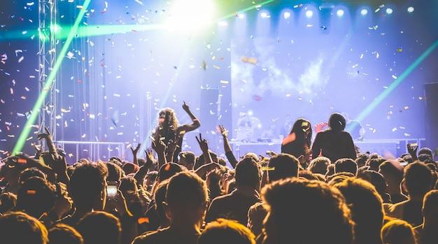 コンサートフェスティバルの夜のクラブで踊る若者 Premium写真