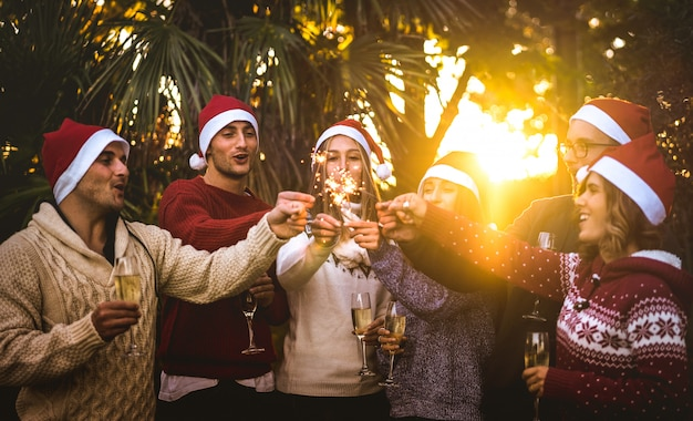 シャンパンワイントースト屋外でクリスマスを祝うサンタ帽子を持つ友人グループ Premium写真