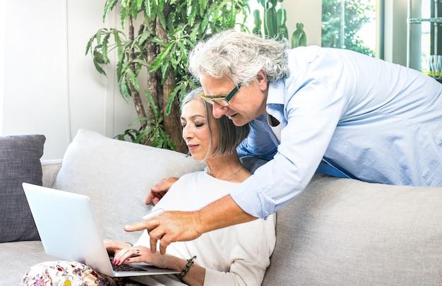 自宅でソファの上にラップトップコンピューターを使用してシニアの引退したカップル Premium写真