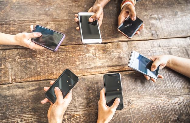 木製の背景にモバイルのスマートフォンを使用している同僚 Premium写真
