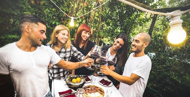 楽しい裏庭のガーデンパーティーで赤ワインを飲んで幸せな友達 Premium写真