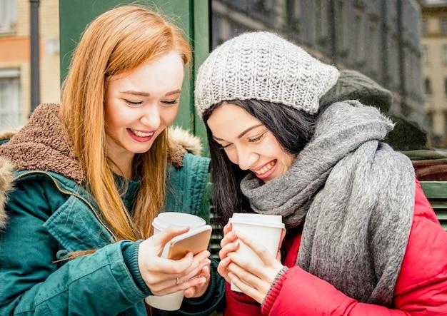 冬の季節にコーヒーテイクアウトカップを楽しんで幸せなガールフレンドの親友 Premium写真