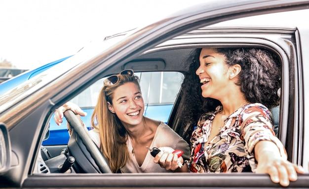 車のロードトリップの瞬間で楽しんで若い女性の親友 Premium写真